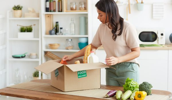 Woman unpacking box containing food
